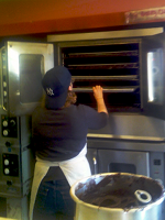 At the bakery - putting cookie sheets in the oven